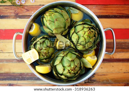 Top view artichokes and lemons in a pot ready to be steamed - stock photo