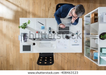 Top view at office. A grey hair businessman sitting at his desk and using a phone. Focus on the table - stock photo