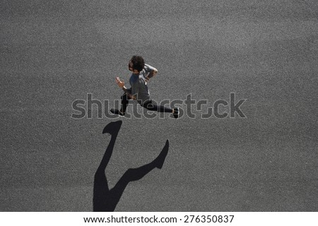 Top view athlete runner training at black road in black sportswear at central position. Muscular fit sport model sprinter exercising sprint on city road. Full body length of Caucasian model. - stock photo