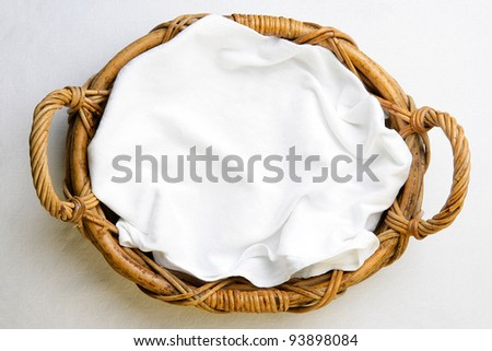 Top view, bakery basket with napkin on the white tablecloth - stock photo