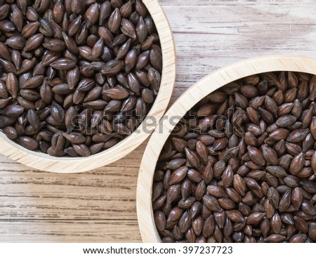 Top view - Beer ingredients, Chocolate malt and Roast malt  on wooden background - stock photo