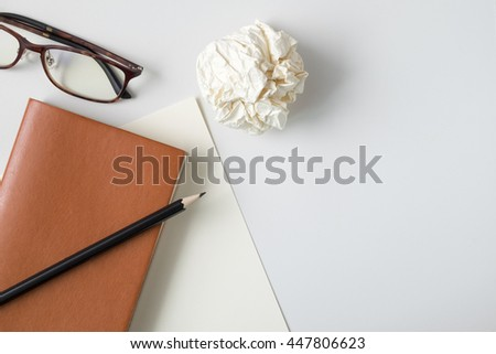 Top view blank orange leather diary, crumpled paper ball, pencil and glasses on white desk - stock photo