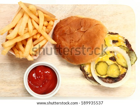Top View Burger and Fries Served on Cutting Board with Ketchup. - stock photo