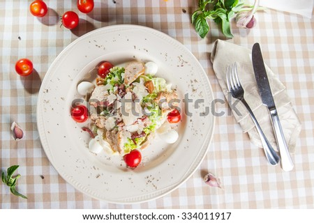 Top view Classical Caesar salad with  roasted chiken, quail eggs, lettuce leaves, becon, parmesan slices and cherry tomatoes on  the white plate on the table with ingredients - stock photo