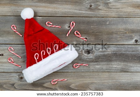 Top view close up of candy canes and Santa hat placed on rustic wood  - stock photo