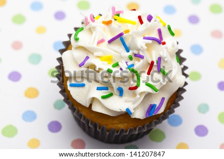 Top view close-up shot of a cupcake garnished with sprinkles. - stock photo