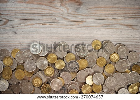 Top view coins on old wooden desk with copy space on top. - stock photo