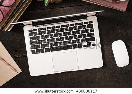 Top view computer laptop and old book with eyeglasses on reading table.  - stock photo