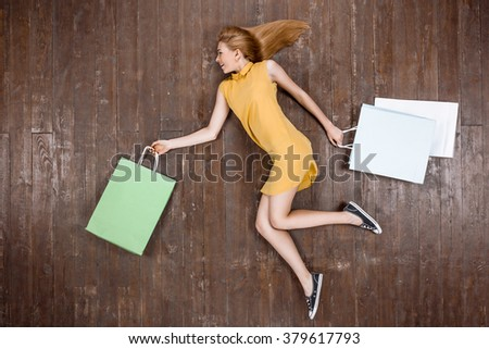 Top view creative photo of beautiful young woman on vintage brown wooden floor. Girl holding shopping bags - stock photo