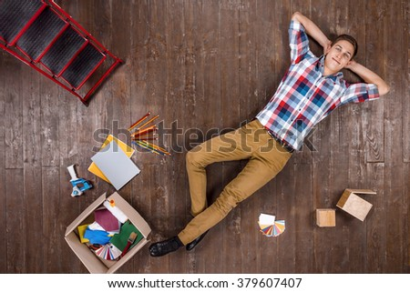 Top view creative photo of handsome young man on vintage brown wooden floor. Man is ready for home renovation - stock photo