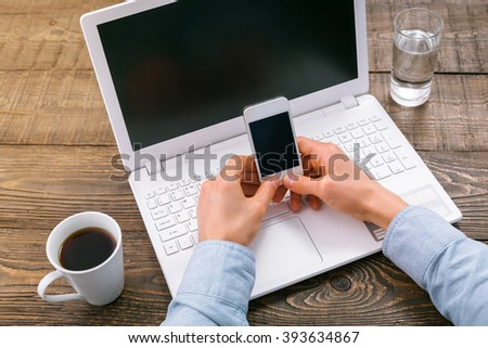 Top view creative photo of objects and hands on vintage brown wooden table. There are glass of water, coffee and laptop on it. Man using mobile phone with space for your logo - stock photo