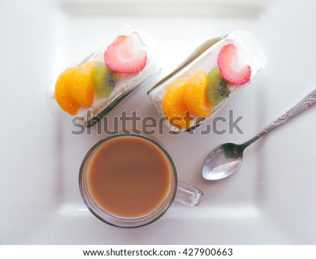 top view cup of coffee and sweet cakes. Cake and coffee. Cake with fruits. Round Cake. Cake close up. Cake on a plate. Homemade Cake. Whole Cake.           - stock photo
