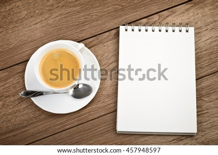 Top view Cup of coffee in a white cup and spiral notepad on wooden background - stock photo