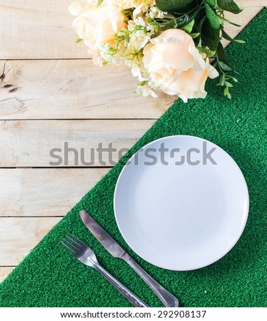 Top view empty plate on wood background with fork and knife - stock photo