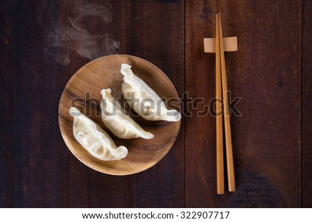 Top view fresh dumplings with hot steams on wood plate with chopsticks. Chinese meal on rustic old vintage wooden background.  - stock photo