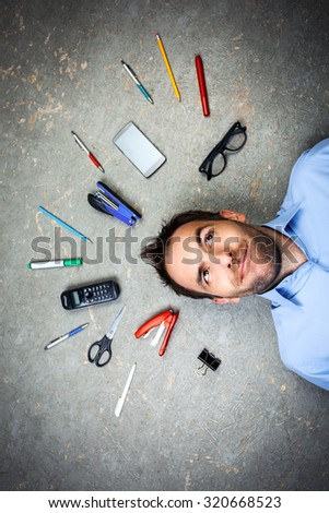 Top view funny photo of businessman with beard wearing shirt. Businessman thoughtfully looking up and lying on floor full of office supplies - stock photo