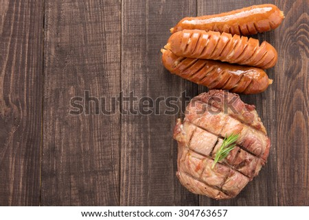 Top view grilled steak and sausage on a wooden background. - stock photo