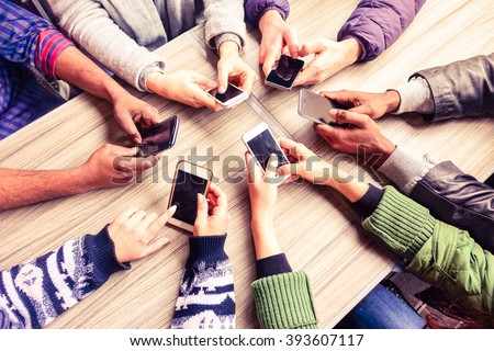 Top view hands circle using phone in cafe - Multiracial friends mobile addicted interior scene from above - Wifi connected people in bar table meeting - Concept of teamwork main focus on left phones - stock photo