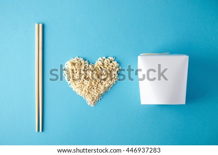 Top view I love wok takeaway noodles presentation with chopsticks, blank box and dry pasta in heart shape isolated on blue mockup - stock photo