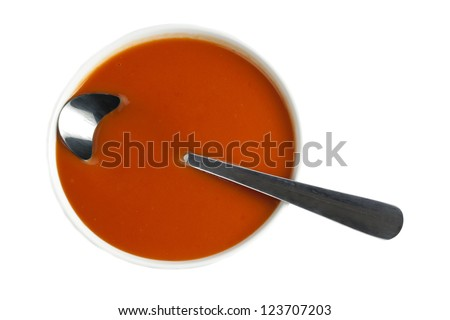 Top view image of a tomato soup bowl with spoon against white background - stock photo