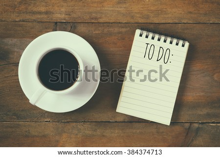 top view image of blank notebook with the text TO DO, next to cup of coffee on wooden desk. vintage filtered and toned  - stock photo