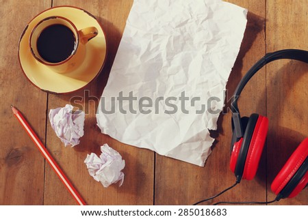top view image of crumpled paper next to headphones and cup of coffee over wooden table - stock photo