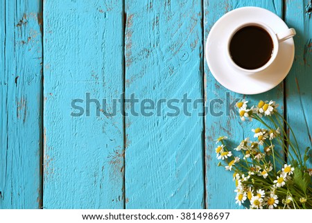 top view image of daisy flowers next to cup of coffee on blue wooden table. vintage filtered and toned - stock photo