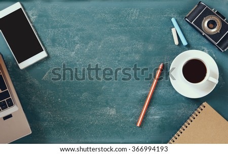 top view image of mobile phone, cup of coffee and laptop over blackboard background  - stock photo