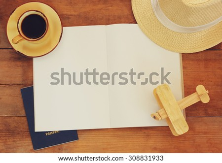top view image of open notebook with blank pages, cup of coffee wicker hat and wooden aeroplane over wooden table. ready for mockup or adding text. travel concept - stock photo