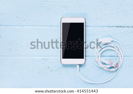 Top view image of smartphone,earphones with blank screen on wooden table. - stock photo