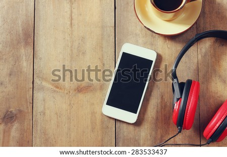 top view image of smartphone with blank screen headphones and coffee cup. room for text - stock photo