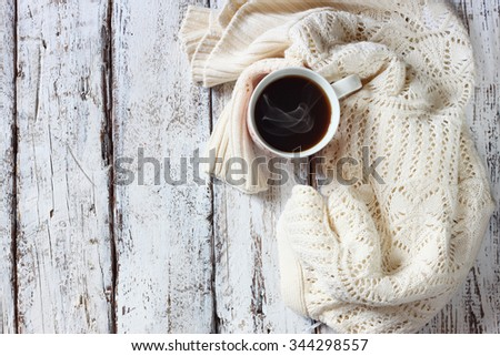 top view image of white cozy knitted sweater with to cup of coffee on a wooden table  - stock photo