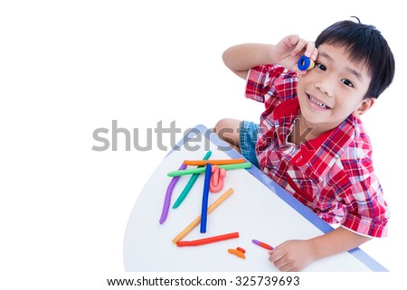 Top view. Little asian boy playing and creating toys from play dough. Child smiling and show his works from clay, isolated on white background. Strengthen the imagination of child - stock photo