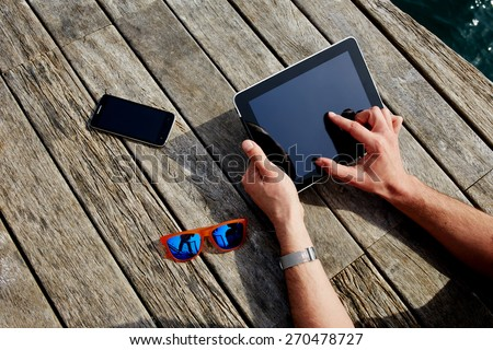 Top view male hands using digital tablet on wooden jetty background, vacation holidays concept, lying smart phone, colorful sunglasses and mans hands with touch pad - stock photo