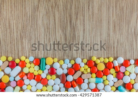 Top view medicine background concept  the many medicine pills,capsules,drugs,tablets on wood table texture background. - stock photo