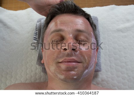 Top view middle age man with facial mask smiling in beauty salon - stock photo