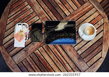 Top view mock-up with touch screen digital tablet, smart phone, bill check with money and cup of coffee on the wooden desk, gadgets with empty blank screen, work break of businessman - stock photo