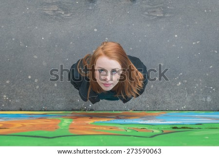 Top view of a beautiful young redhead girl posing in the city streets - stock photo