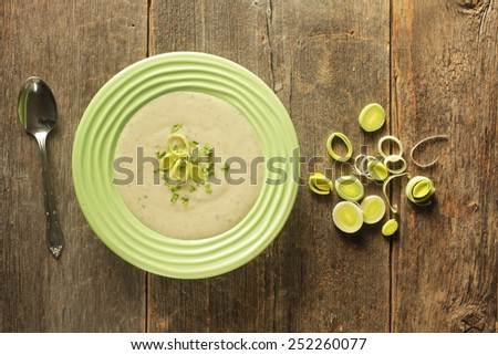 Top view of a bowl of leek soup with fresh leek rings on a wooden background - stock photo