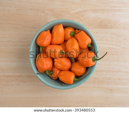Top view of a bowl of orange habanero peppers on a wood kitchen counter top. - stock photo