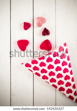 Top view of a candy cone decorated with pink hearts spilling heart shaped gummy candies over a white wooden board table - stock photo