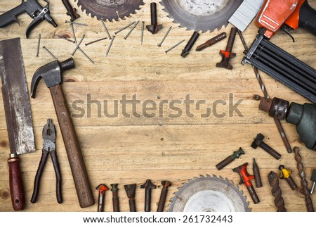 Top view of a carpenter's wooden table with many types of tools - stock photo