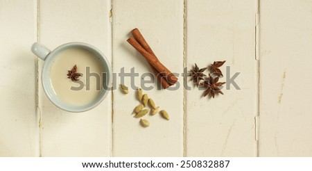 Top view of a chai tea with cinnamon, anise and cardamom on a white wooden background - stock photo