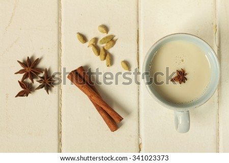 Top view of a chai tea with cinnamon, anise and cardamom on a wooden background - stock photo