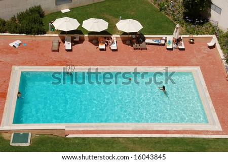 Top view of a condo swimming pool with two empty white deckchairs. - stock photo