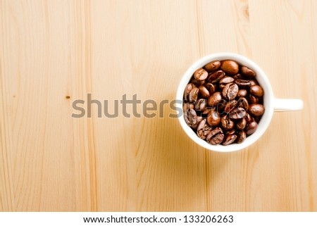 top view of a cup of coffee beans with space for text over wood background - stock photo