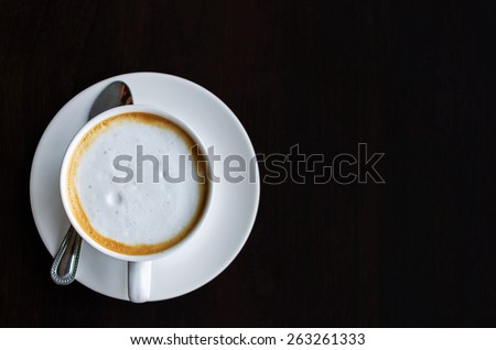 Top view of a cup of coffee, cappuccino on a wooden table. - stock photo