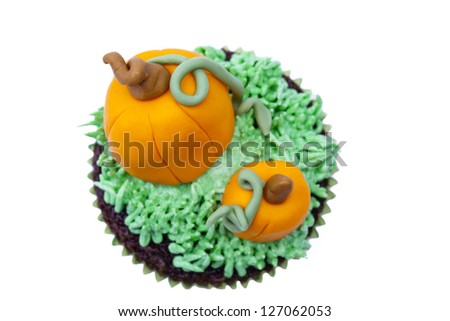 Top view of a cupcake decorated with pumpkin miniature overt white background. - stock photo