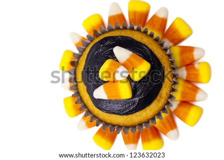 Top view of a cupcake garnished with candy corn and chocolate cream. - stock photo