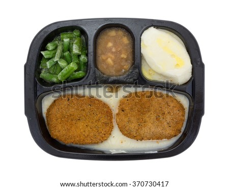 Top view of a frozen fried chicken patties TV dinner with potatoes, green beans and apples in sauce on a white background. - stock photo